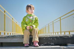 liten flicka på trappan ser bort foto