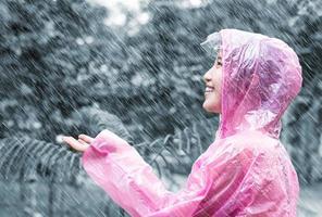 asiatisk kvinna i rosa regnrock njuter av regnet i trädgården foto