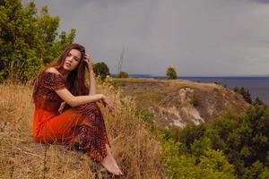 kvinna som sitter ensam nära havet foto