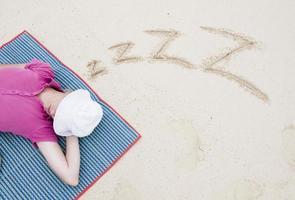 flicka som sover på stranden foto