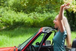 glad blondin njuter av sin röda cabriolet foto