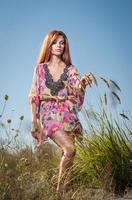 dam i mångfärgad klänning som tycker om naturen foto