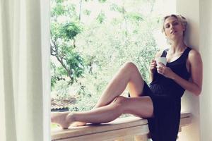 vacker kvinna njuter av sitt morgonkaffe foto