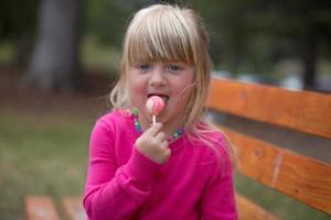liten flicka som tycker om en lolly pop. foto