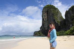 kvinna njuter av tillflyktsort promenader längs stranden