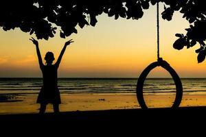 flickan njuter av friheten vid solnedgångstranden. foto