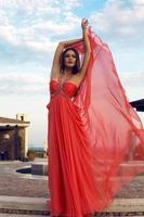 vacker kvinna i lyxig röd klänning poserar på park