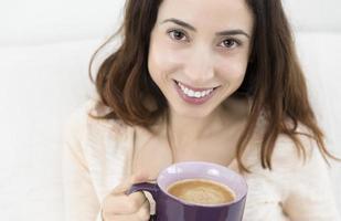 attraktiv kvinna njuter av sin kopp kaffe foto