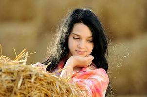 vacker flicka som tycker om naturen i höet foto