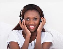 kvinna njuter av musik genom hörlurar i sängen foto