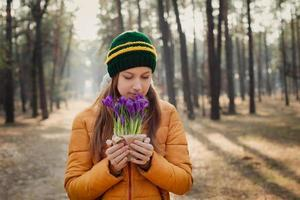 glad kvinna njuter av lukten av vårblommor foto