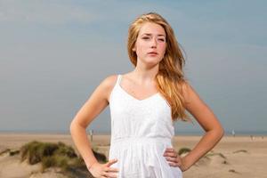 vacker flicka som bär vit klänning och njuter av naturen. foto