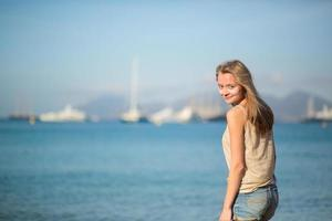 ung flicka njuter av sin semester vid havet foto