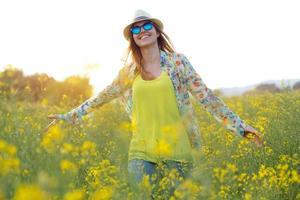 vacker ung kvinna njuter av sommaren i ett fält.
