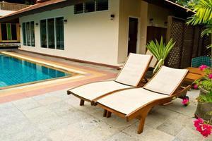 långa stolar vid poolen foto