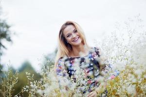 skönhet flicka som tycker om naturen, blond flicka i klänning på en foto