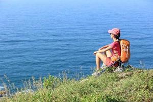 vandrare för ung kvinna njuter av utsikten på bergstoppen vid havet foto