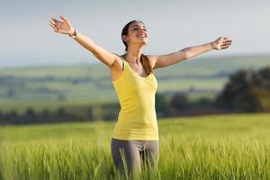 ung kvinna njuter av våren som står i ett spannmålsfält foto