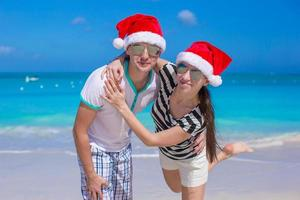 porträtt av unga par i santa hattar njuta av strandsemester foto