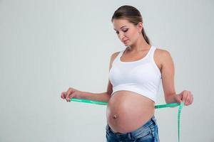 porträtt av en gravid kvinna med måttband foto