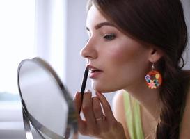 ung vacker kvinna som sminkar nära spegeln foto