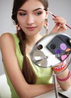 ung vacker kvinna som sminkar nära spegeln, sitter vid foto