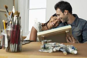 par som tittar på målning i konstnärstudio foto