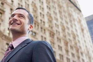 affärsman som ler mot suddig byggnad foto