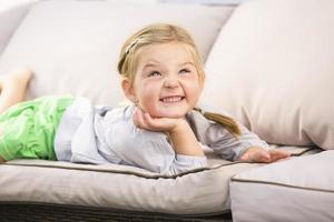 ung flicka som ligger på soffan och ler foto