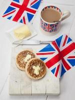 smörde engelska crumpets med kopp te och union jacks foto