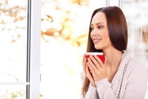 attraktiv ung dam som håller en kopp foto