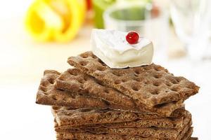 staplad fullkornsbröd med mjuk ost och vinbär foto