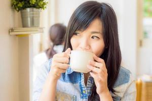 kvinna med kopp kaffe ler i caféet foto