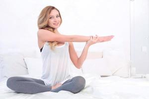 kvinna som sträcker sin kropp i sängen foto