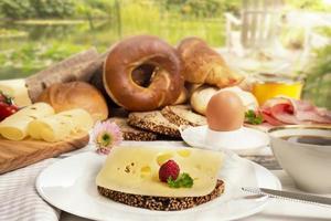frukost med ostbröd, kaffe, ägg, skinka, sylt i trädgården foto