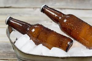 kall flaska öl på is foto