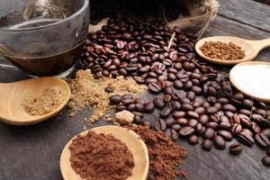 riven kaffe i sked på rostade kaffebönor bakgrund foto
