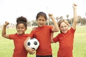 unga flickor som spelar på ett fotbollslag foto