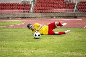 målvakt fångar fotbollen foto
