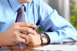 affärsman som gör affärer, sitter vid sitt skrivbord på kontoret,
