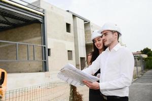 verkställande arkitekt man kvinna övervakar byggarbetsplatsen med ritning foto