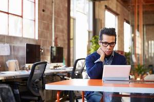 designer sitter vid mötesbordet som arbetar på den digitala surfplattan foto