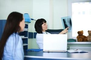 unga kvinnor och läkare tittar på röntgen foto