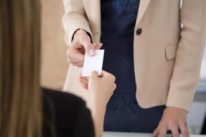 affärskvinna som ger sitt visitkort till sin partner foto