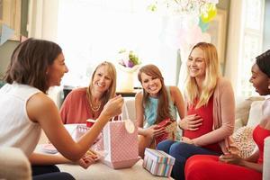 grupp kvinnliga vänner som möts för baby shower hemma foto