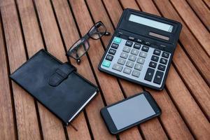 mobiltelefon, anteckningsblock, glas på träbord. foto