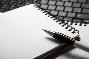 penna på en anteckningsbok i en cell och tangentbord foto