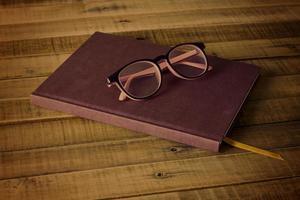 bok med glasögon på träbakgrunden foto