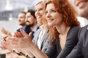 leende kvinna som klappar händer bland andra leende kollegor foto