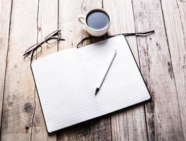 glas på anteckningsboken med penna och kopp kaffe foto